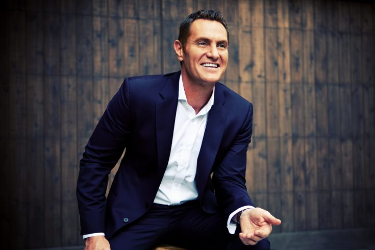 Darren Hardy in Front of a Wooden Background