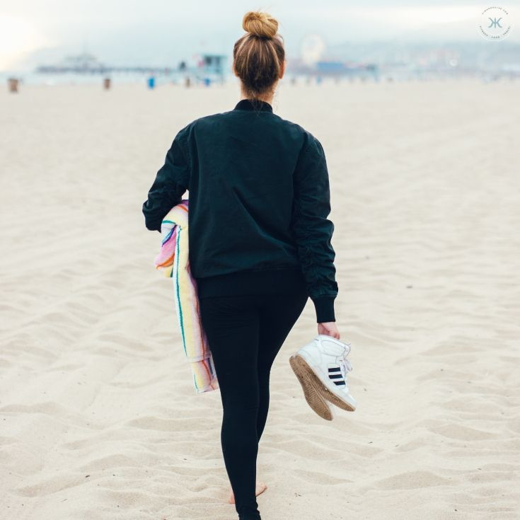 girl walking on the beach after implementing a couple of these online jobs for college students