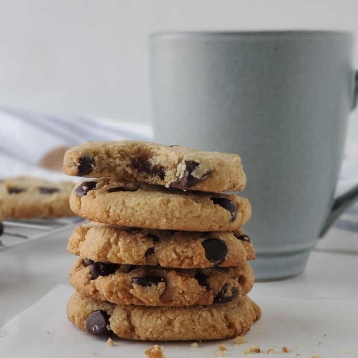 Keto Chocolate Chip Cookies stacked with a mug behind them