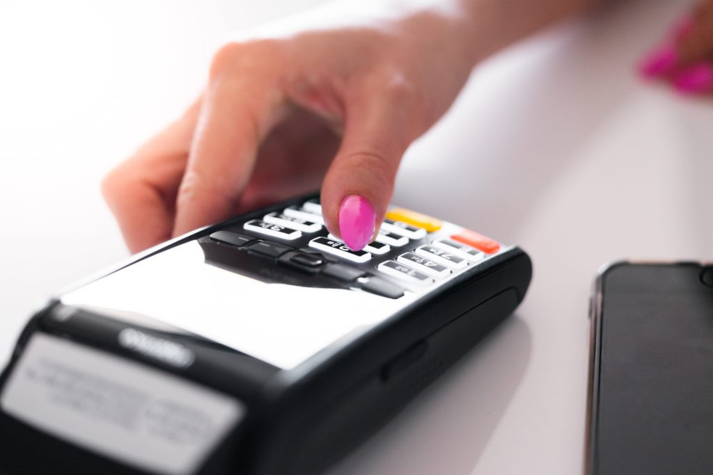 woman's hand on a credit card machine