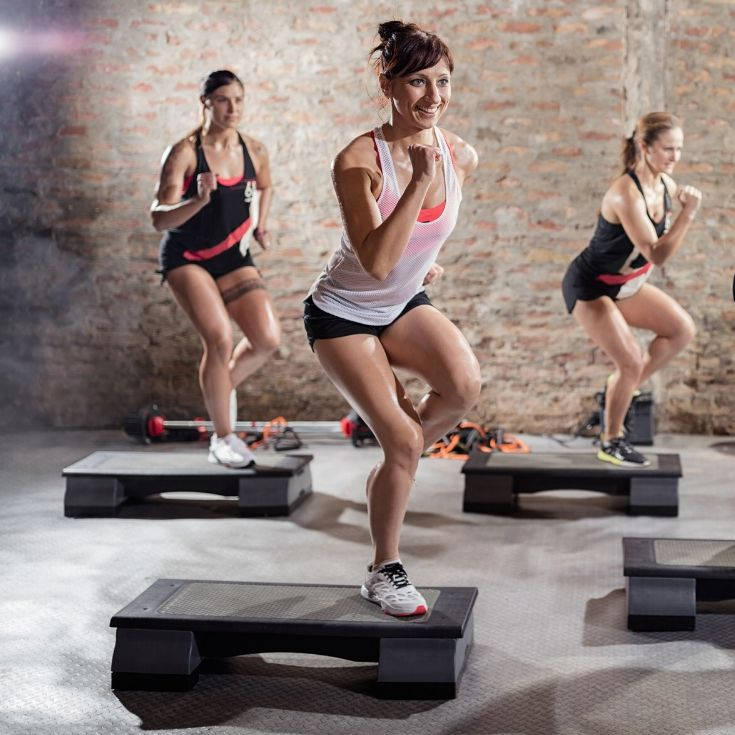 3 Women doing LES MILLS BODYSTEP workouts on exercise steps