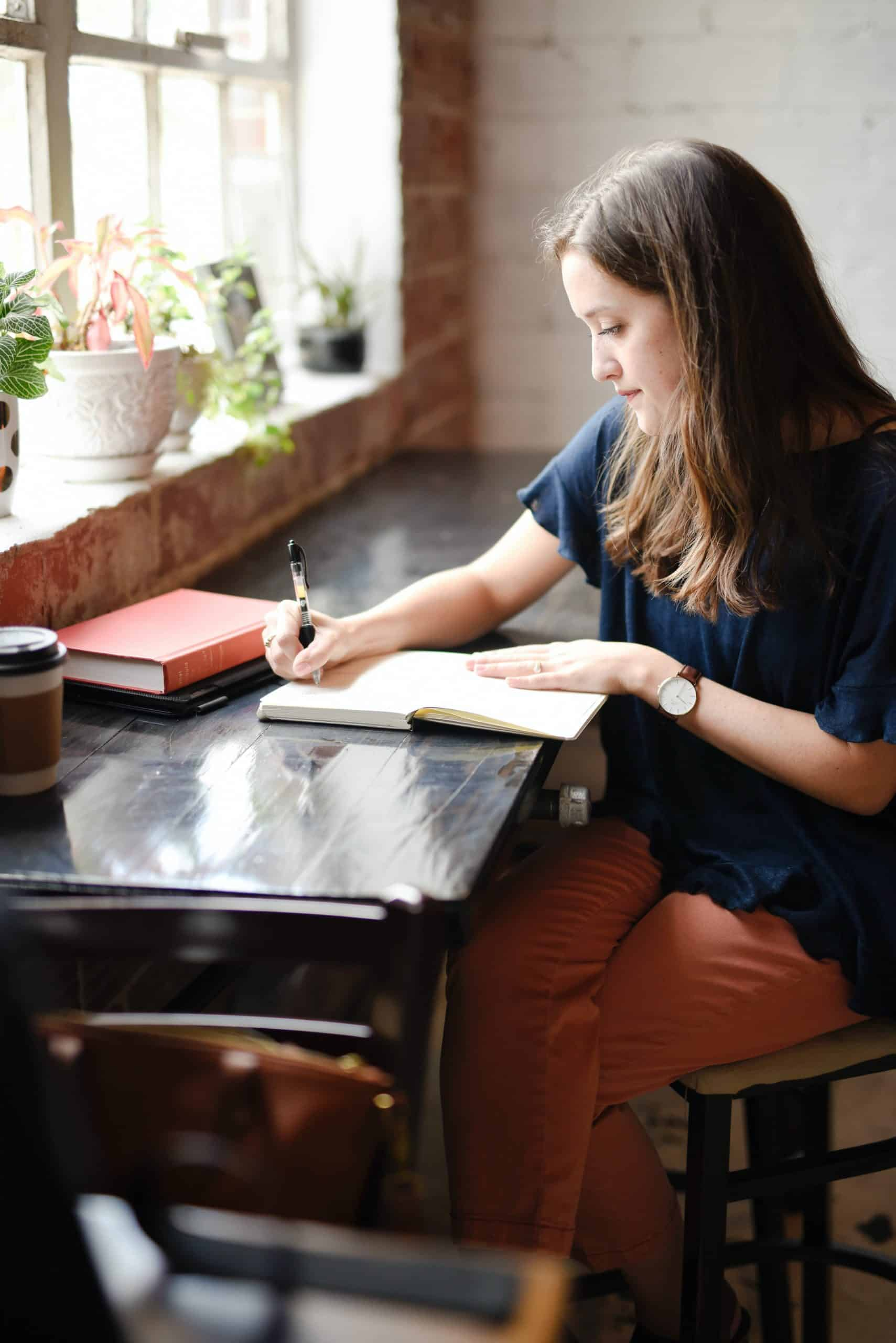 woman sitting at a desk journaling