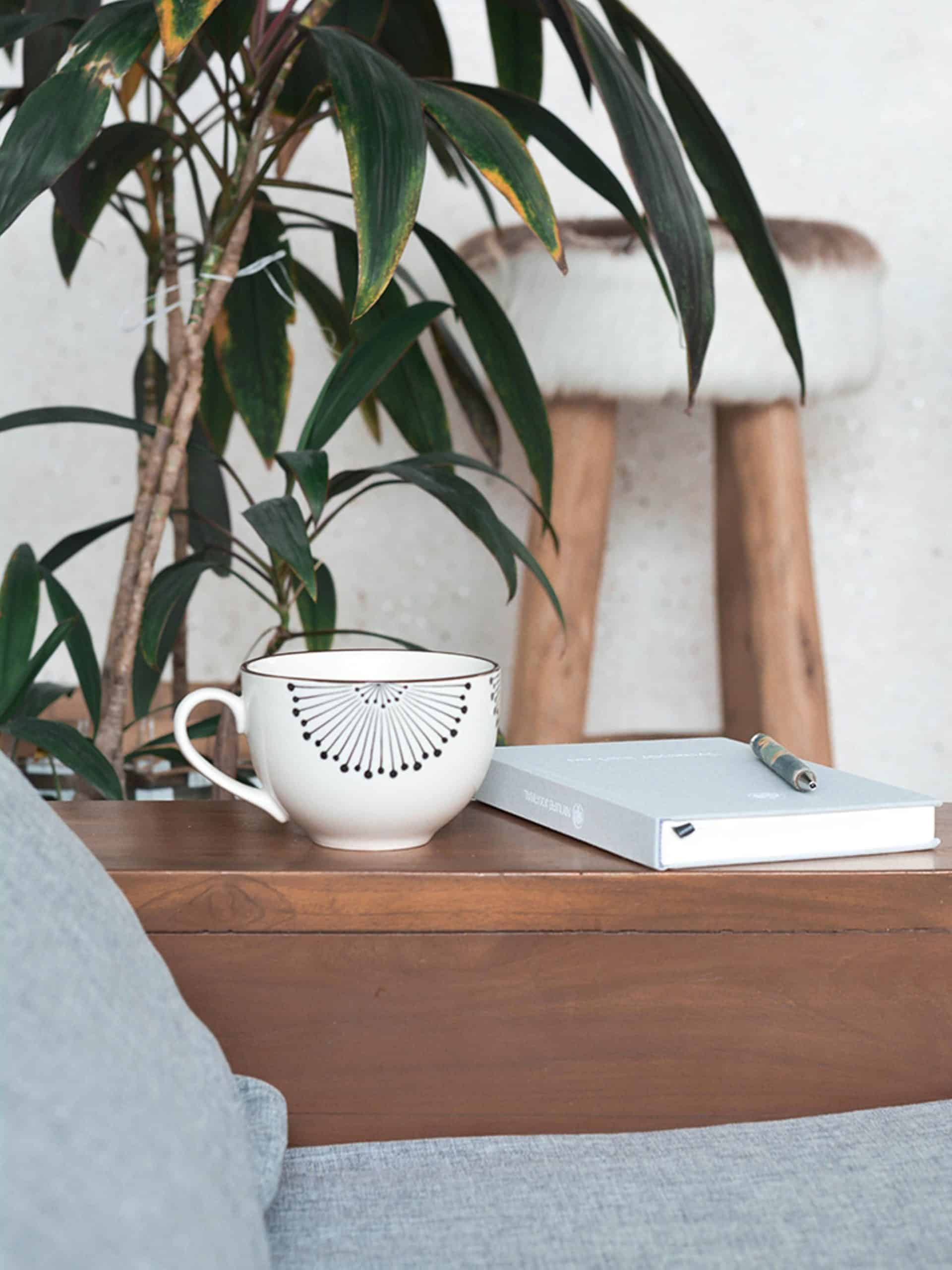 journal next to coffee cup on a side table