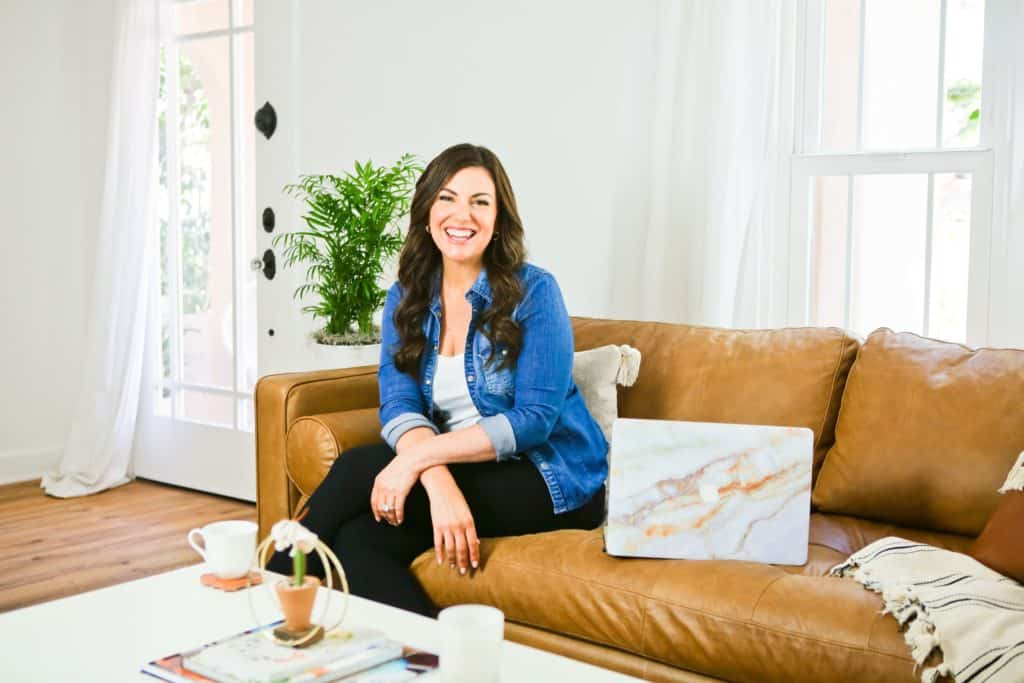 Amy Porterfield sitting on the couch with laptop