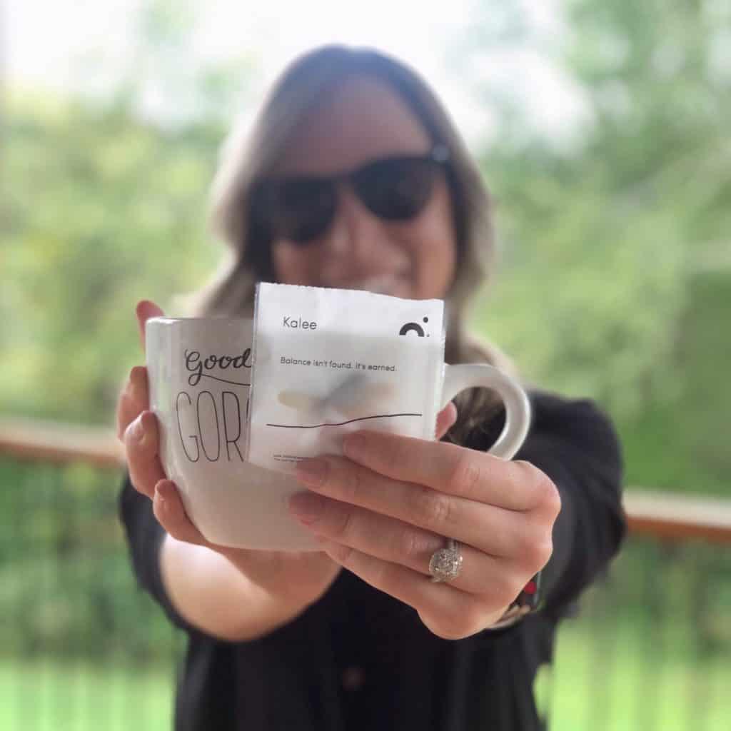 Kalee holding a mug and customized vitamin pack