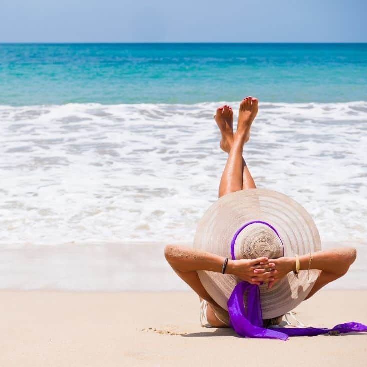woman relaxing on the beach repeating affirmations for confidence