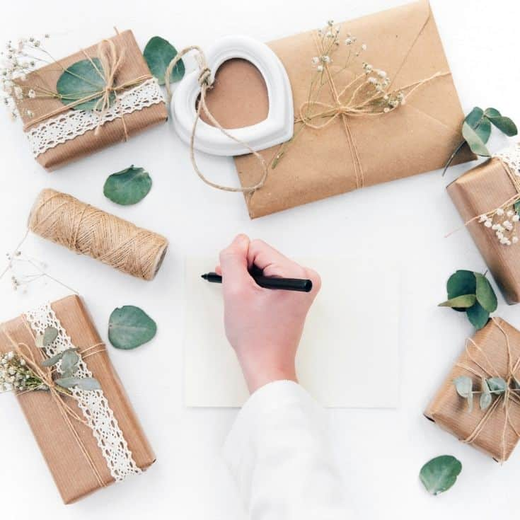 individually wrapped gifts and person starting to write a letter