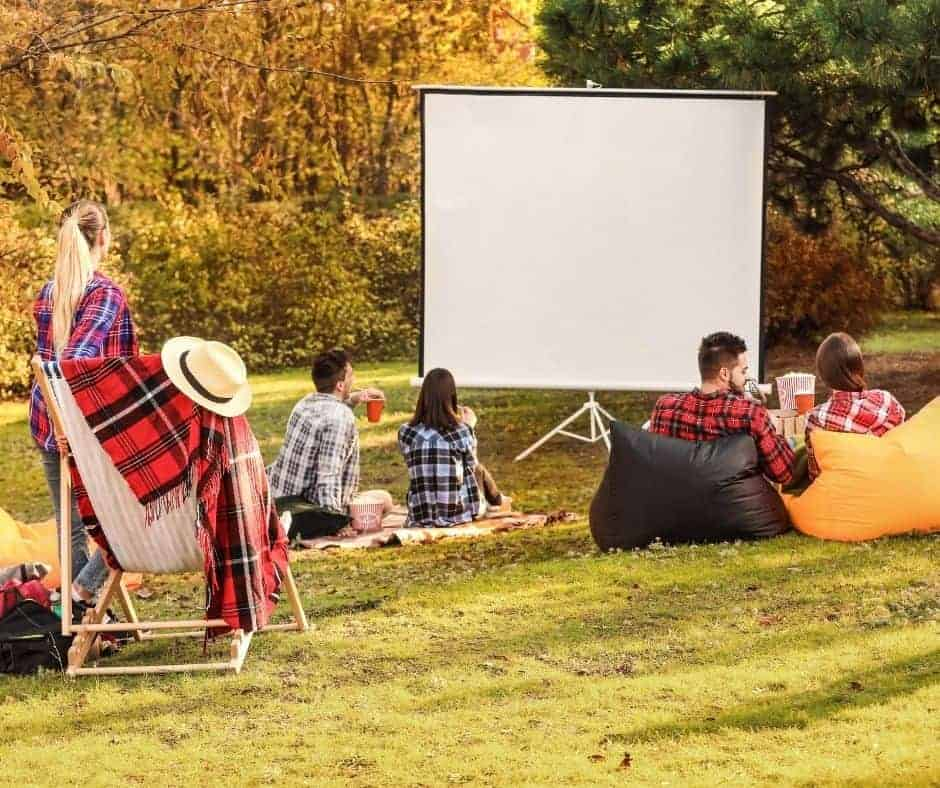 young people getting ready to watch a movie outdoors