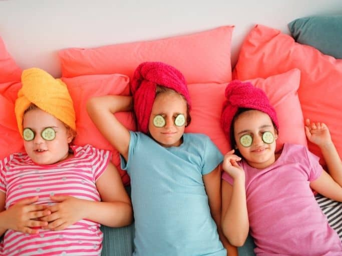 three little girls with hair in towels and eyes covered with cucumbers