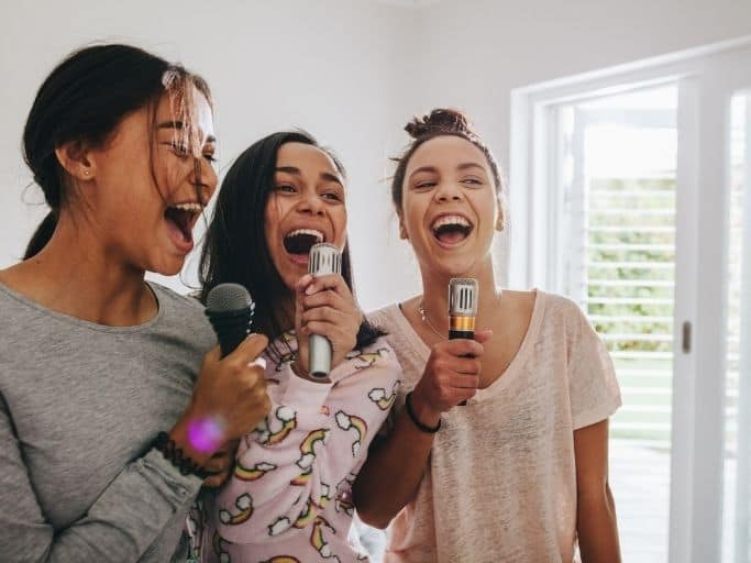 three girls singing into microphones