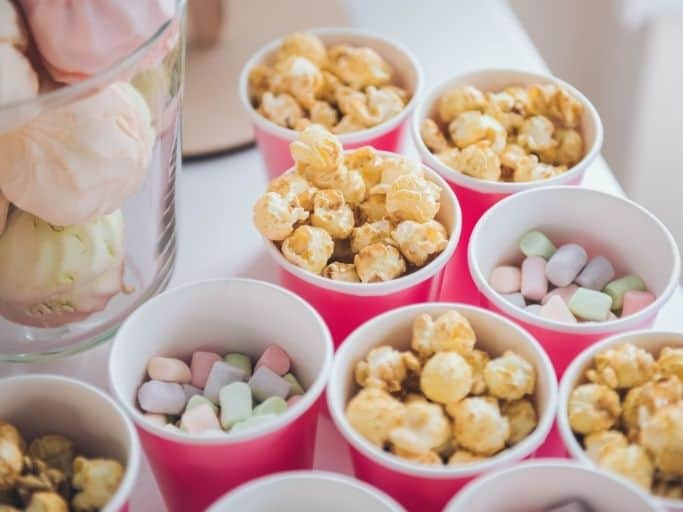 popcorn bar with different options of popcorn and candy in each pink cup