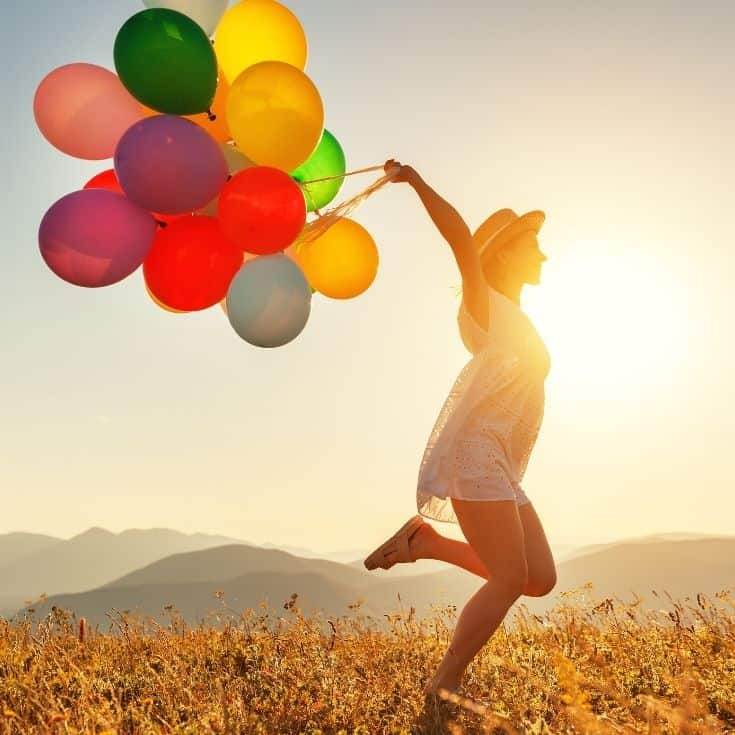 woman with a bunch of balloons running outside