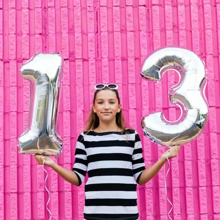 girl holding 13th birthday balloons