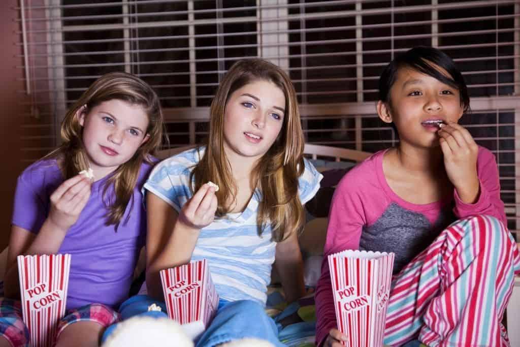 3 tweens watching a movie