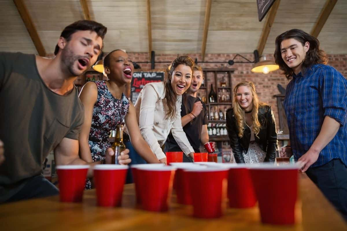 drinking game - people playing beer pong